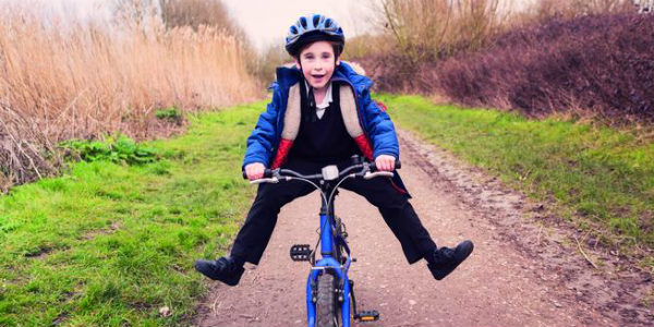 Image of A Happy and Charming Boy Riding A Bicycle.